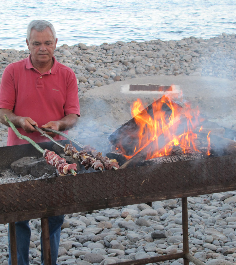 local man grilling espetada at feast in madeira